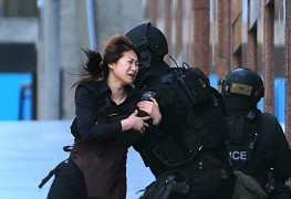 A hostage runs to armed tactical response police officers for safety after she escaped from a cafe under siege at Martin Place in the central business district of Sydney, Australia, Dec. 15