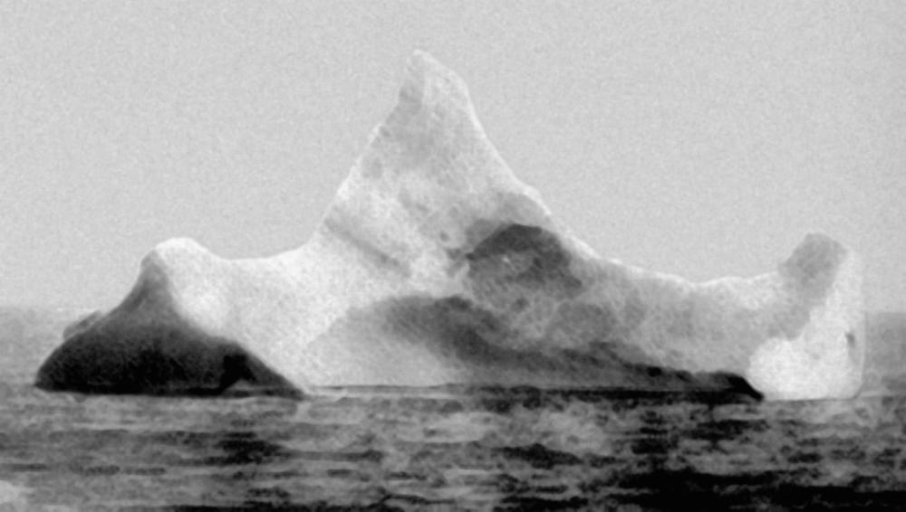 The iceberg to the right is the one that is claimed to have hit the Titanic. It has a red streak of paint and dent fit